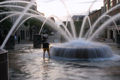 Child in the fountain. Blur of a child playing in a multiple fountian Royalty Free Stock Photography