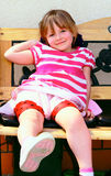 A child of four years. Girl sitting on a bench day in the park Royalty Free Stock Photo