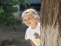 A child of four years peeping from behind a tree. The girl with a smile peeked out from behind a tree on the left side Stock Photography