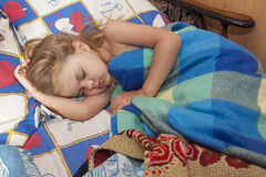 A child of four years sleep in a bed with an old sheets and blankets Royalty Free Stock Photography