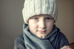 Child is freezing cold. Boy (child, teen, kid) in warm hat and scarf and is freezing cold Royalty Free Stock Image
