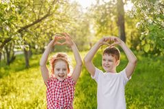 Child friend folded her hands a heart shaped. Cute little girl and boy friend folded her hands a heart shaped Royalty Free Stock Image
