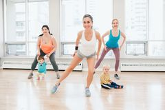 Child-friendly fitness for mothers with kids toddlers. Group of three young women with children doing workout in gym class with instructor to loose baby weight stock photography