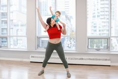 Child-friendly fitness for mothers with kids toddlers. Young women with child doing workout in gym class to loose baby weight. Child-friendly fitness for mothers stock images