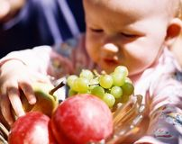 Child with fruit. In flowering summer garden near mom (softfocus Stock Photo