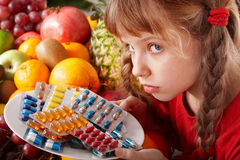 Child with fruit and vitamin pill. Stock Photography