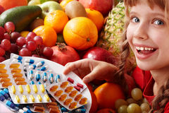 Child with fruit and vitamin pill. Royalty Free Stock Photos