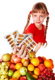 Child with fruit and vitamin pill. Stock Photo