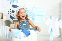 Child fun happy little girl  to wash clothes and laughs in laund. Child fun happy little girl  to wash clothes and laughs in the laundry room Stock Photos