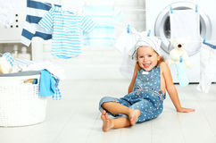 Child fun happy little girl to wash clothes and laughs in laund royalty free stock photo