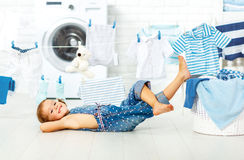 Child fun happy little girl to wash clothes and laughs in laund royalty free stock images