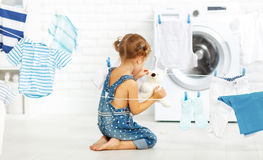 Child fun happy little girl  to wash clothes and teddy bear in l Stock Images