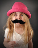 Child with Fun Mustache Disguise. A little child is holding a pretend mustache disguise for a humor or fun concept. The girl is smiling and happy with a pink hat Stock Photography