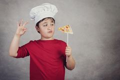 Child funny cook with slice pizza. On gray background royalty free stock photography