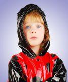 Child with funny face  in rain coat. Stock Photos