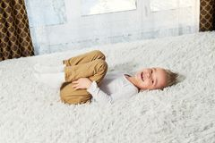 Child funny home. Happy boy blond lying on soft bedspread bed, top view. Little kid laughing while looking at camera. Child funny home. Happy boy blond lying on stock image