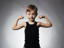 Child. Funny Little Boy.Sport Handsome Boy showing his hand biceps muscles Stock Photo