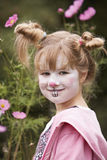 Child with funny make up. Portrait of smiling young girl at garden with funny rabbit make-up Stock Images