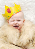 Child in a fur cape and crown on a white background. baby crying royalty free stock photography