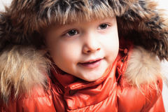 Child in fur hat and orange jacket. fashion kid.children.close-up.winter style Stock Photography