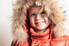 Child in fur hood and orange winter jacket. fashion kid.children.close-up Stock Images