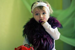 Child with fur on shoulders chews gift Royalty Free Stock Photography