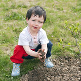 Child garden. An outdoor portrait of a cute child playing with earth soil in a garden Stock Image