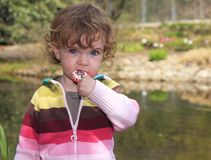 Child in the garden. A child having a lollipop on the river bank Royalty Free Stock Images