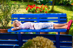 Child in garden lying on bench Stock Photo
