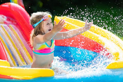 Child in garden swimming pool with slide. Child playing in inflatable baby pool. Kids swim, slide and splash in colorful garden play center. Happy little girl Stock Image