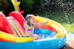 Child in garden swimming pool with slide. Child playing in inflatable baby pool. Kids swim, slide and splash in colorful garden play center. Happy little girl Stock Images