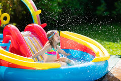 Child in garden swimming pool with slide. Child playing in inflatable baby pool. Kids swim, slide and splash in colorful garden play center. Happy little girl Royalty Free Stock Photography