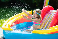 Child in garden swimming pool with slide. Child playing in inflatable baby pool. Kids swim, slide and splash in colorful garden play center. Happy little girl Royalty Free Stock Photos