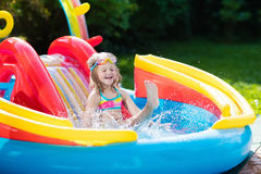 Child in garden swimming pool with slide. Child playing in inflatable baby pool. Kids swim, slide and splash in colorful garden play center. Happy little girl Royalty Free Stock Images