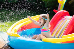 Child in garden swimming pool with slide. Child playing in inflatable baby pool. Kids swim, slide and splash in colorful garden play center. Happy little girl Stock Photo