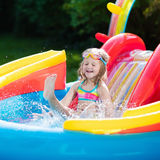 Child in garden swimming pool with slide. Child playing in inflatable baby pool. Kids swim, slide and splash in colorful garden play center. Happy little girl Royalty Free Stock Photo