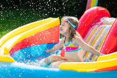 Child in garden swimming pool with slide. Child playing in inflatable baby pool. Kids swim, slide and splash in colorful garden play center. Happy little girl Stock Photos