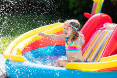 Child in garden swimming pool with slide Stock Photos