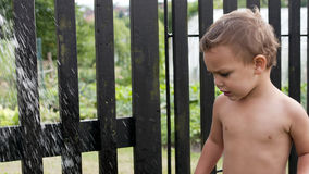Child with garden water shower Royalty Free Stock Photos