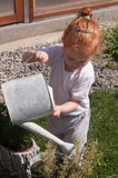 Child gardener. Little girl watering the flowers in the pot with watering can royalty free stock images
