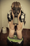 Child in gas mask sitting on toilet. Single male child in gas mask sitting on toilet in bathroom with pants down and hands on face royalty free stock image