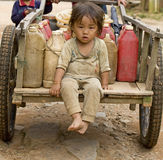 Child with gasoline can. Sitting on a cart, Laos Royalty Free Stock Photos
