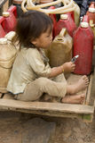 Child with gasoline can. Sitting on a cart, Laos Stock Images