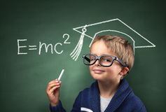Child genius in education. Child holding piece of chalk with E=mc2 and mortar board drawing on blackboard concept for genius student, university education and royalty free stock photography