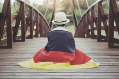 Child with german flag. On wooden bridge stock image
