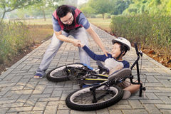 Child gets crash and helped by dad Royalty Free Stock Image
