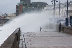 A child gets soaked by a huge wave at  Porthcawl, South Wales, UK. Royalty Free Stock Image