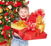 Child with gift box near Christmas tree. Isolated Royalty Free Stock Photos