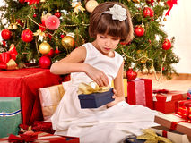 Child with gift box near Christmas tree. Royalty Free Stock Image