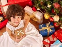 Child with gift box near Christmas tree. royalty free stock photos